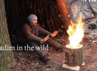 Vadim in the wild happily sitting near swedish fire torch in the forest of Ukraine.